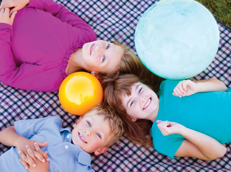 Three young children laying on their backs on a plaid blanket all are smiling