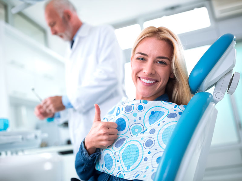 Dental patient sitting in dental chair giving a thumbs-up while doctor is in the backgound working.